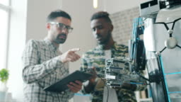 Slow motion of guys testing robot with tablet, smart machine moving arm