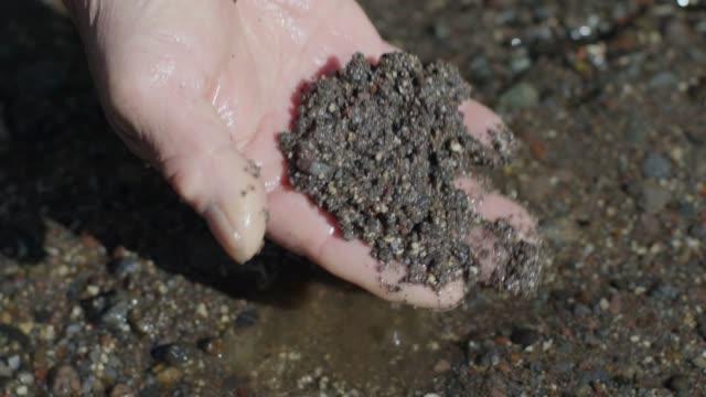 vídeos de stock e filmes b-roll de slow motion of hand digging wet soil - porta amostra