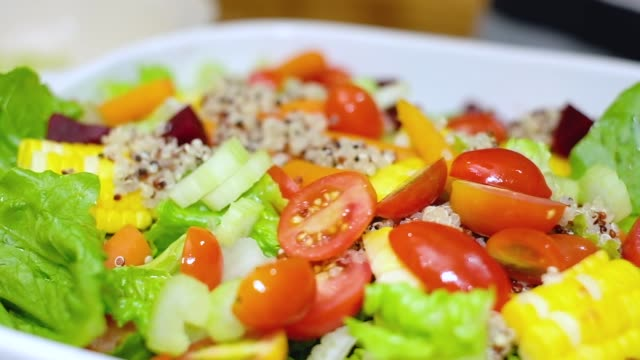 slow motion of hand drop fresh slice tomato on mix vegetable salad in white bowl in kitchen counter. - quinoa salad stock videos & royalty-free footage