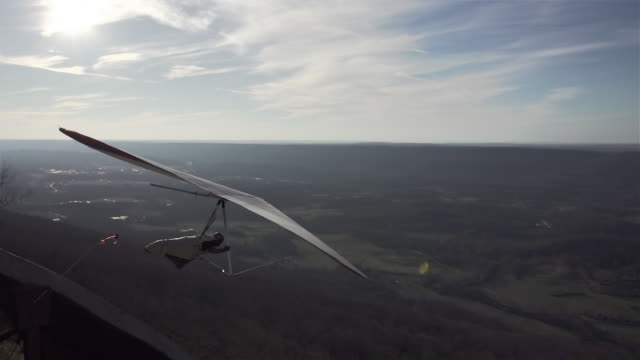 Slow Motion of Hang Glider Takes Off from Summit at Sunset