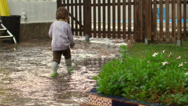 slow motion of happy child playing, jumping and smiling under the rain - ein junge in gummistiefel stock-videos und b-roll-filmmaterial