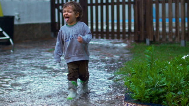 Slow motion of happy child playing, jumping and smiling under the rain