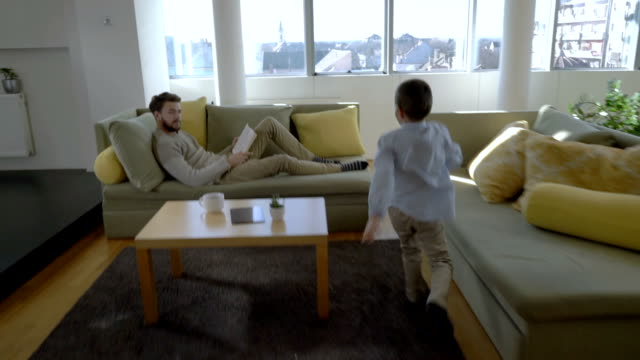 Slow motion of happy little boy running to his father who is reading a book on the sofa.