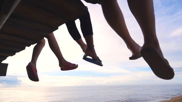 vídeos de stock, filmes e b-roll de velocidade lenta de mãe feliz e sua filha sentada em um cais de madeira e balançar os pés sobre a água - pendurar