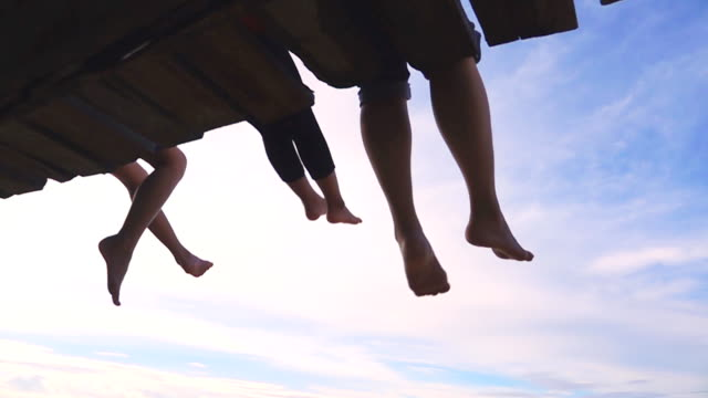 slow motion of happy mother and her daughter sitting on a wooden pier and dangle feet over the water - hanging stock videos & royalty-free footage