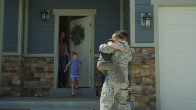 slow motion of happy wife and children greeting soldier returning home from duty / lehi, utah, united states - armed forces stock videos & royalty-free footage