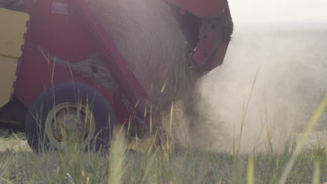 slow motion of hay bail being released from machine - hay stock videos & royalty-free footage