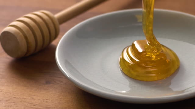 Slow motion of Honey falling on plate