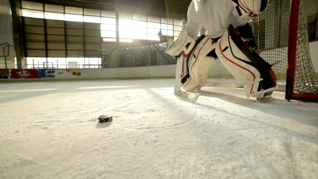 Slow motion of ice hockey goalie trying to defend his goal on a match during the game.