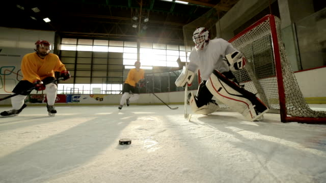 Slow motion of ice hockey player shooting at goal and scoring while goaltender is trying to block the shot.