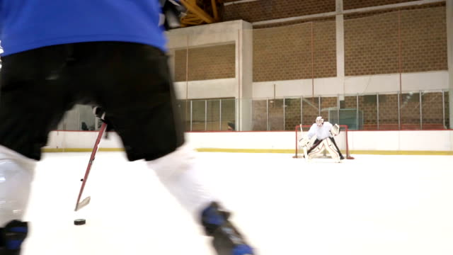 Slow motion of ice hockey player taking a shoot but failing to score a goal at the arena.