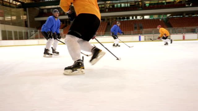 Slow motion of ice hockey players tackling and scoring a goal while playing match in the arena.