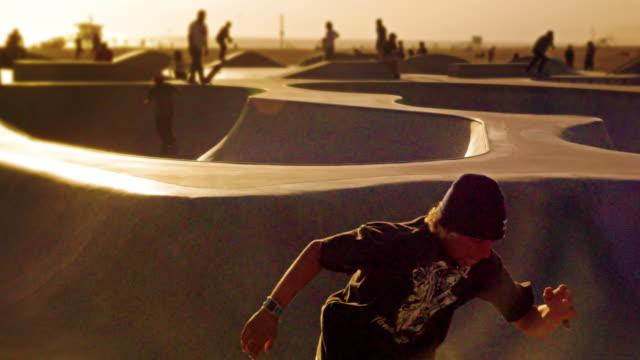 Slow motion of jumping skateboarder wearing beanie at the skate park near Venice Beach, California