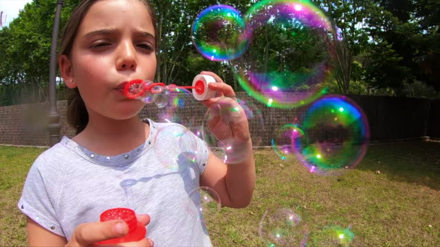 Slow motion of kids making soap bubbles.