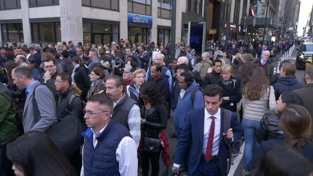 slow motion of large group of commuters crossing street in new york city at rush hour - population explosion stock videos & royalty-free footage