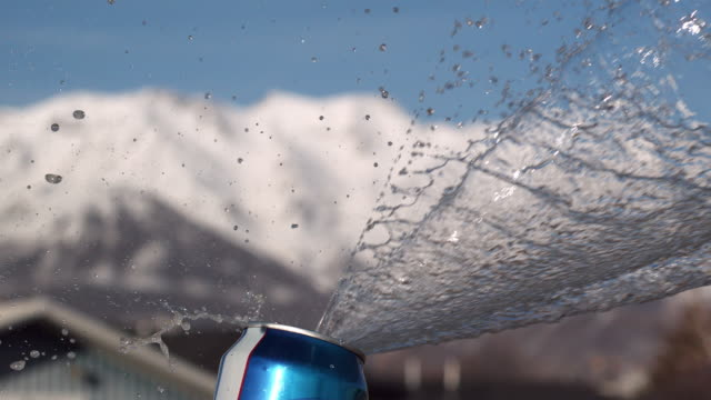 stockvideo's en b-roll-footage met slow motion of liquid spraying out of aluminum can with snow covered mountains in the background. - aluminium