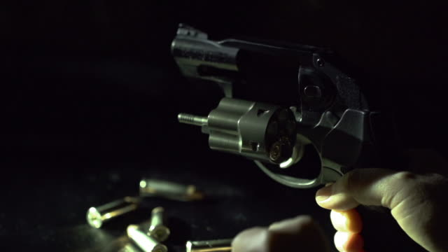 slow motion of loading bullet into revolver - handgun stock videos and b-roll footage