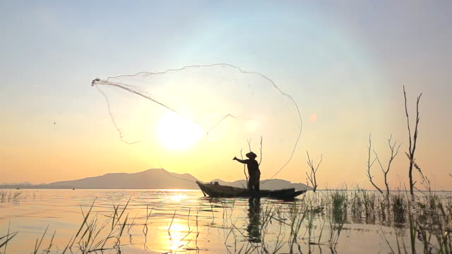 slow motion of local lifestyles of fisherman at lagoon sunset - fisher role stock videos & royalty-free footage