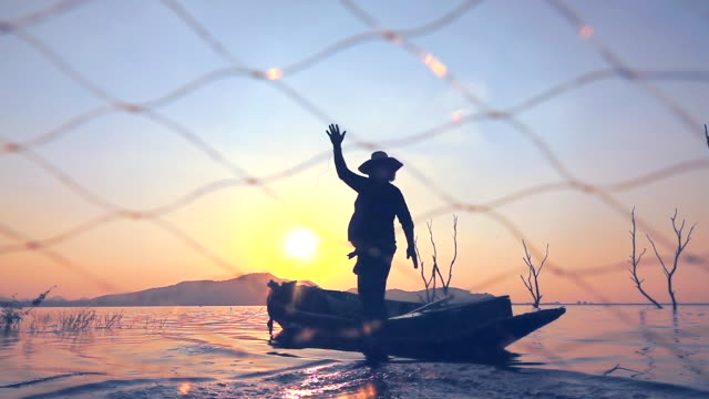 slow motion of local lifestyles of fisherman at lagoon sunset - fishing net stock videos & royalty-free footage