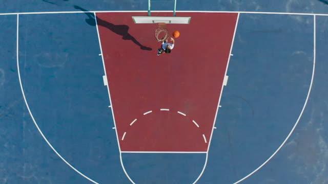 vidéos et rushes de mouvement lent du joueur de basket-ball mâle lançant avec succès une bille dans le cerceau sur le court - joueur de basket ball