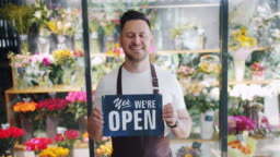 Slow motion of male florist holding we are open slate standing in flower store