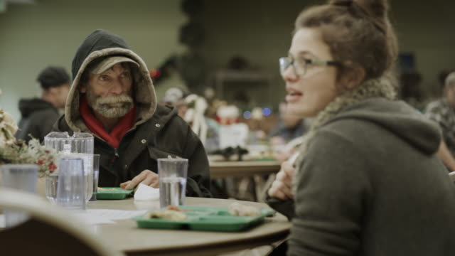 vidéos et rushes de slow motion of man and woman eating meal and talking in homeless shelter / provo, utah, united states - mal logés