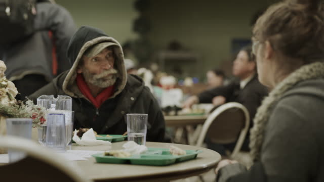 slow motion of man and woman eating meal and talking in homeless shelter / provo, utah, united states - hemlöshet bildbanksvideor och videomaterial från bakom kulisserna