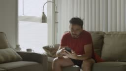 Slow motion of man at home scrolling on cell phone and looking bored