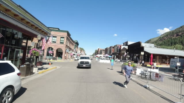 slow motion of man exercising and people walking dog on the street in telluride, colorado, america amid the 2020 global coronavirus pandemic - colorado stock videos & royalty-free footage