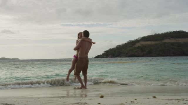 slow motion of man holding and twirling woman on ocean beach / jamesby island, tobago cays, st. vincent and the grenadines - badbyxor bildbanksvideor och videomaterial från bakom kulisserna