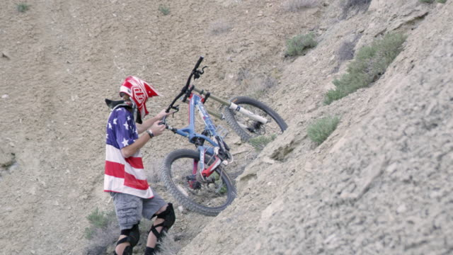 slow motion of man pushing mountain bike up hill. - elbow pad stock videos & royalty-free footage