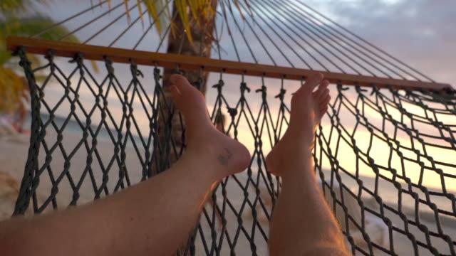 vídeos de stock, filmes e b-roll de slow motion of man relaxing on hammock at beach against sky, legs male tourist lying during sunset - montego bay, jamaica - rede de dormir