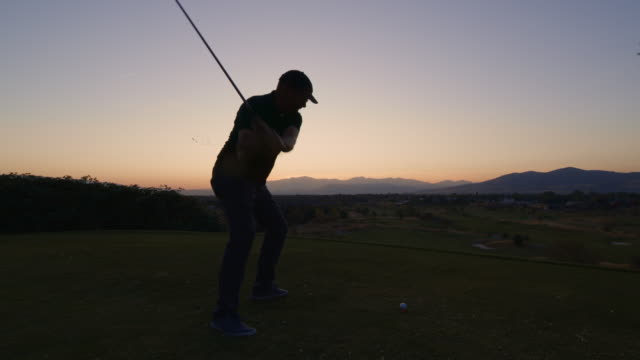 slow motion of man teeing off on golf course at sunset / cedar hills, utah, united states - landscaped stock videos & royalty-free footage