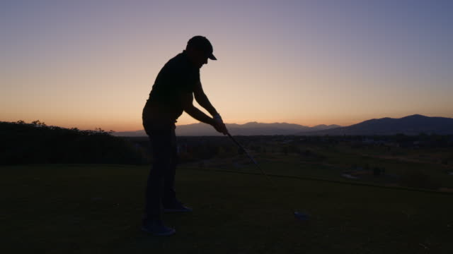 slow motion of man teeing off on golf course at sunset then throwing golf club / cedar hills, utah, united states - tee off stock videos & royalty-free footage