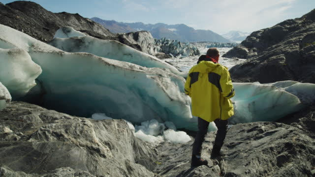 slow motion of man walking on glacier and photographing scenic view,  / palmer, alaska, united states - cappotto invernale video stock e b–roll