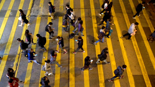 Slow motion of many people using smart phone while walking the zebra crossing road