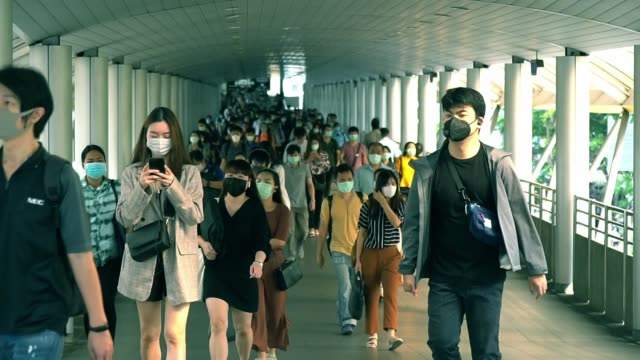 slow motion of many people wears mask walk on bridge rush hour after worker at public mass transit system at chong-nonsi bts station, bangkok thailand. - elevated walkway stock videos & royalty-free footage
