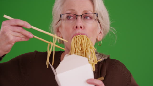 stockvideo's en b-roll-footage met slow motion of mature woman messily eating noodles on greenscreen - long beach californië