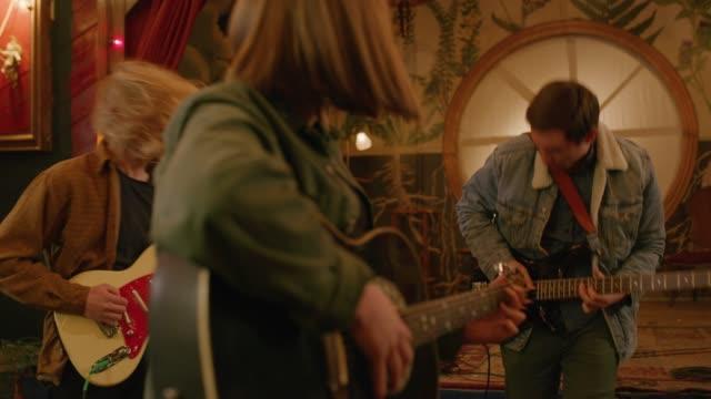 vídeos y material grabado en eventos de stock de slow motion of men and woman practicing playing guitars in nightclub / provo, utah, united states - provo
