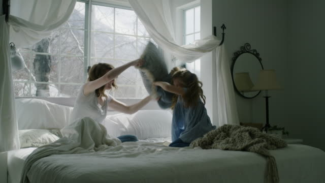 vidéos et rushes de slow motion of mother and daughter having pillow fight in bed / pleasant grove, utah, united states - oreiller