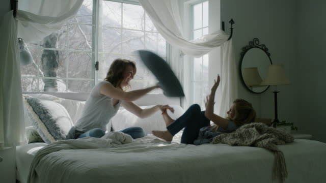 slow motion of mother and daughter having pillow fight in bed / pleasant grove, utah, united states - erkerfenster stock-videos und b-roll-filmmaterial