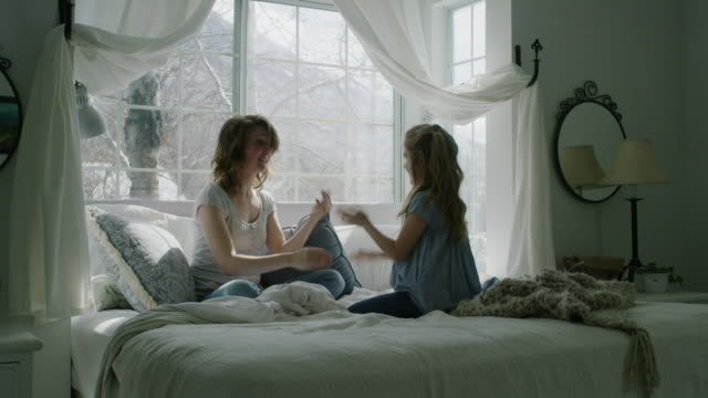 vídeos de stock, filmes e b-roll de slow motion of mother and daughter playing hand clapping game in bed / pleasant grove, utah, united states - janela saliente