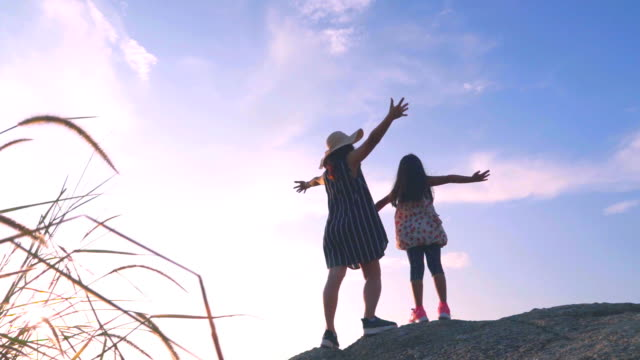 Slow motion of Mother and daughter standing on the top of the hill sunset