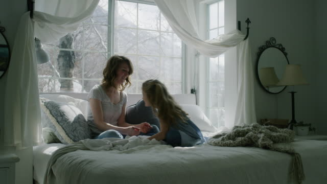 slow motion of mother and daughter talking in bed then hugging bed near bay window / pleasant grove, utah, united states - erkerfenster stock-videos und b-roll-filmmaterial