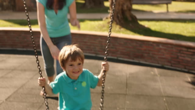 slow motion of mother pushing son on swing in park. - swing play equipment stock videos and b-roll footage