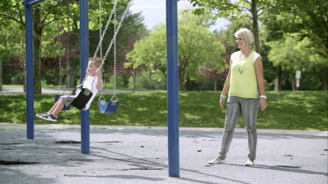 Slow motion of mother pushing young son in swing.