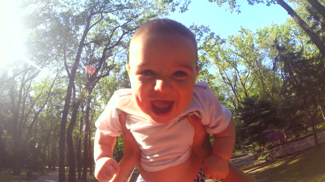 slow motion of mother throwing his adorable a son in the air. - life events stock videos & royalty-free footage