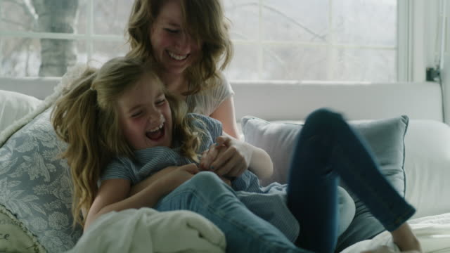 slow motion of mother tickling daughter in bed near window / pleasant grove, utah, united states - kitzeln stock-videos und b-roll-filmmaterial