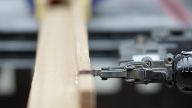 slow motion of nail gun nailing into boards - nail stock videos & royalty-free footage