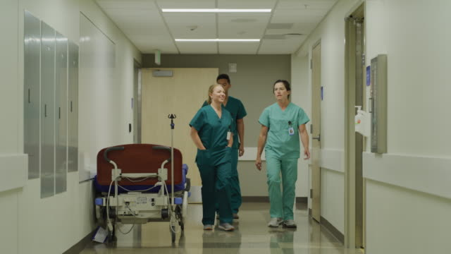 Slow motion of nurses walking and talking in hospital corridor / Salt Lake City, Utah, United States